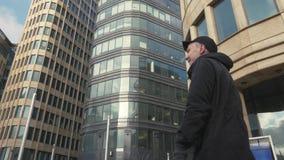 Hombre en casquillo negro que camina en la calle de la ciudad y la mano que agita para los saludos metrajes