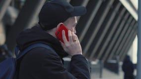 Hombre en casquillo y chaqueta negros que habla por el teléfono elegante en paisaje urbano del fondo almacen de video