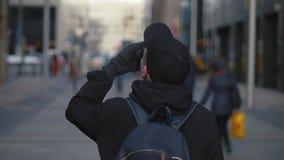 Hombre en casquillo y mochila negros que bebe el café caliente durante caminar en la calle de la ciudad metrajes