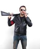 Hombre en chaqueta de cuero, gafas de sol y cigarro negros con el arma Imagen de archivo libre de regalías