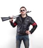 Hombre en chaqueta de cuero, gafas de sol y cigarro negros con la escopeta Imagen de archivo