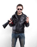 Hombre en chaqueta de cuero, gafas de sol y cigarro negros con la escopeta Imagenes de archivo