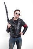 Hombre en chaqueta de cuero y gafas de sol negras con la escopeta Fotografía de archivo