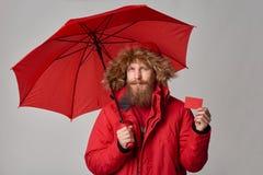 Hombre en chaqueta del invierno con el paraguas que muestra la tarjeta del crédito en blanco foto de archivo