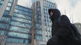 Hombre en chaqueta negra con la capilla en la calle de la ciudad de la cabeza que camina y de la mochila almacen de video