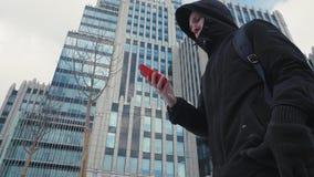 Hombre en chaqueta y mochila negras usando el teléfono móvil y el caminar en la calle de la ciudad metrajes