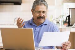 Hombre en cocina con la computadora portátil y el papeleo fotos de archivo libres de regalías