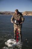 Hombre en control de la perforación del camo en hielo con el taladro Imagenes de archivo