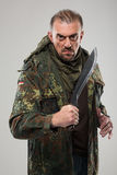 Hombre en cuchillo que se sostiene uniforme del soldado fotografía de archivo