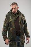 Hombre en cuchillo que se sostiene uniforme del soldado foto de archivo