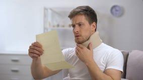 Hombre en cuello cervical de la espuma que lee la cuenta médica chocada con el precio alto, salud almacen de video