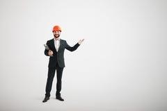 Hombre en desgaste formal y un casco de la construcción que señalan en el dir Imagen de archivo libre de regalías