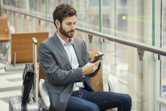 Hombre en el aeropuerto del pasillo Mensaje de texto que mecanografía en el teléfono móvil Fotos de archivo libres de regalías
