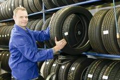 Hombre en el almacén del neumático con un neumático Imagen de archivo