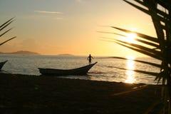 Hombre en el barco en la puesta del sol Foto de archivo libre de regalías