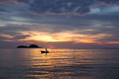 Hombre en el barco en la puesta del sol Imágenes de archivo libres de regalías