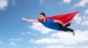 Hombre en el cabo rojo del super héroe que vuela sobre el cielo azul Imágenes de archivo libres de regalías