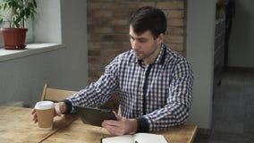 Hombre en el café de consumición de la mañana y trabajo en la tableta almacen de video