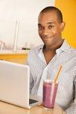 Hombre en el café usando la computadora portátil Imágenes de archivo libres de regalías