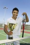 Hombre en el campo de tenis que sostiene el retrato del trofeo imagen de archivo