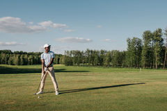 Hombre en el casquillo que detiene al club de golf y que golpea la bola en césped verde imágenes de archivo libres de regalías
