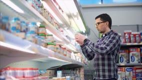 Hombre en el centro comercial que elige los alimentos para niños almacen de metraje de vídeo