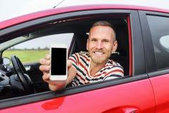 Hombre en el coche que muestra el teléfono elegante Fotografía de archivo libre de regalías