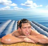 Hombre en el colchón de la playa Imagenes de archivo