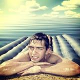 Hombre en el colchón de la playa Fotos de archivo