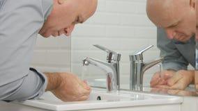 Hombre en el cuarto de baño que se lava las manos y la cara con el agua dulce en fregadero imagenes de archivo