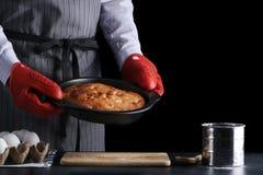 Hombre en el delantal que sostiene la empanada recientemente cocida en fondo oscuro empanada o torta del od de la receta imagen de archivo libre de regalías