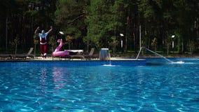 Hombre en el desgaste de Santa Claus que salta en piscina metrajes