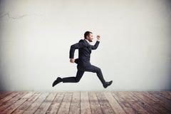 Hombre en el desgaste formal que corre y que salta con sonrisa feliz Imagen de archivo