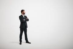Hombre en el desgaste formal que mira al lado con sus brazos cruzados Fotos de archivo