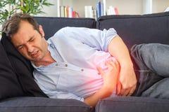 Hombre en el dolor de estómago de la sensación del dolor después del ardor de estómago fotografía de archivo libre de regalías
