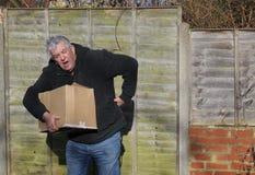 Hombre en el dolor que lleva la caja pesada Tensión trasera Fotos de archivo libres de regalías
