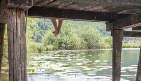 Hombre en el embarcadero con las piernas abajo Foto de archivo libre de regalías