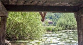 Hombre en el embarcadero con las piernas abajo Fotografía de archivo