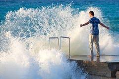 Hombre en el embarcadero contra la onda grande Imagen de archivo