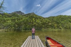 Hombre en el embarcadero en el lago Fotografía de archivo
