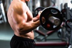 Hombre en el entrenamiento de la pesa de gimnasia en gimnasio Fotos de archivo libres de regalías