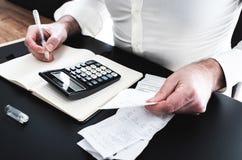Hombre en el escritorio con la calculadora, cuentas o resbalones y notpad de las ventas fotografía de archivo