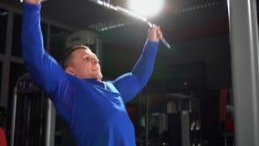 Hombre en el gimnasio, manos de entrenamiento del tríceps El hombre levanta al peso pesado en el gimnasio Hombre fuerte de los de almacen de video