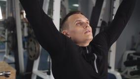 Hombre en el gimnasio que hace ejercicio del peso M?sculos de entrenamiento masculinos del tr?ceps de los brazos usando la m?quin metrajes