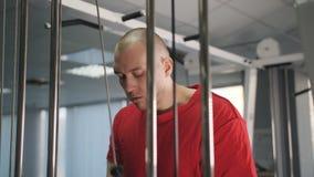Hombre en el gimnasio que hace el ejercicio del peso para el vídeo del primer de los brazos 4k Músculos de entrenamiento del tríc metrajes
