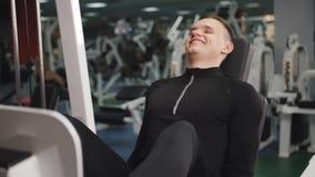 Hombre en el gimnasio que hace el v?deo del ejercicio 4k del peso Músculos de entrenamiento masculinos de los muslos de la pierna almacen de video