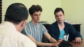 Hombre en el grito enojado de la red de pelo en dos visitantes en la reunión de la oficina metrajes