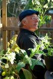 Hombre en el jardín que parece satisfecho Imagen de archivo