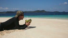 Hombre en el jugo de consumición del coco de la playa almacen de metraje de vídeo