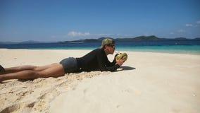 Hombre en el jugo de consumición del coco de la playa almacen de video